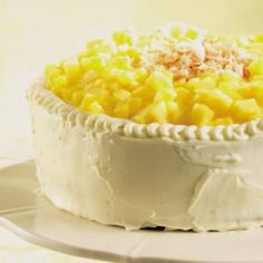 "Pineapple-Coconut Layer Cake -- Winner of ""Best Dessert"" and created by the EatingWell Test Kitchen. In this stunning dessert, two layers of coconut-flavored cake are filled with sweet pineapple curd and topped with creamy coconut frosting, chunks of fresh pineapple and toasted coconut. @EatingWell"