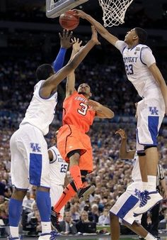 """""""No soup for you!"""" says Anthony Davis of Kentucky as he swats away a layup attempt by Louisville's Peyton Siva. Kentucky goes on to win for a ticket to the finals."""