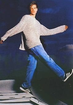 Leo DiCaprio wearing a huge sweater, light wash jeans, and adidas