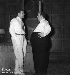 """Producer David O. Selznick (left) talks with director Alfred Hitchcock on the set of """"Rebecca"""", 1939. When """"The Lady Vanishes"""" was released in America and became a huge hit, Selznick signed Hitchcock to a seven year contract in March of 1938. However, Selznick was addicted to amphetamines and a hands-on producer. He would constantly interfere with Hitchcock's vision for the movie and the pair would have a contentious working relationship for their future projects. David O Selznick, Hollywood Party, Alfred Hitchcock, On Set, How To Become, Relationship, Couple Photos, Lady, March"""