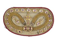 This parure or set of matching jewellery made of gold is set with tourmalines and consists of a pendant cross, pair of bracelets and earrings. It is housed in its original case. Such sets were very popular in the mid 19th century and were made and sold by leading jewellers in London. c 1860  - Museum of London