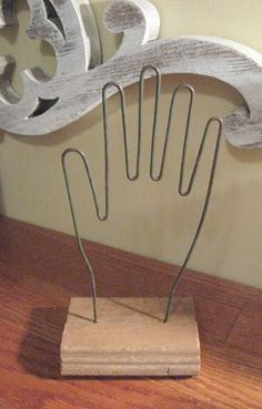 Seems simple enough to duplicate. An old glove stretcher made of wire and  sandwiched between 2 pieces of trim,  glued together in a clamp. This is a great site with many ways to repurpose old found items into useful objects.