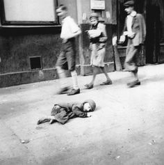 Warsaw Ghetto: A starving child lies on the sidewalk a few breaths away from death. Passers by just pass by. Life was worth less than a slice of bread.