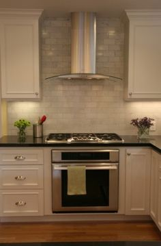 The kitchen features white cabinets, with black marble countertops, and stainless steal appliances.