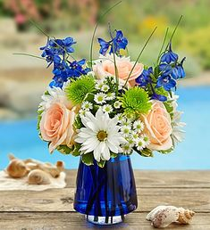 Summer Dunes™ in Blue Cobalt Vase If our truly original arrangement calls to mind a classic Summer scene of sun and sand, then the stunning vase it arrives in completes the picture with the soothing blue of the ocean. Our expert florists gather the freshest roses, delphinium, poms and bear grass in a cool cobalt blue glass vase to help you express yourself perfectly, no matter what the occasion.