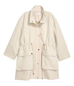 Beige. Jacket in thick fabric with a high stand-up collar, low-dropped shoulders, and a wind flap at front with metal snap fasteners. Patch pockets with