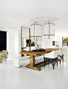 Dining room with large sheer pendants, white ceilings, and a wood table