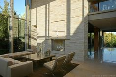 Award-winning modern country estate in Dallas has glossy tile flooring, a textured stone wall with built-in fireplace, a leather lounge, Barcelona chairs, double heigh ceilings and a wall of glass.