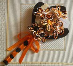 Ramo de 6 flores realizadas en cordón de raso en tonos marfil, beig, naranja, salmón y chocolate, realizado sobre base de fieltro en dos colores a juego con las flores y terminado con una cinta de raso en naranja.