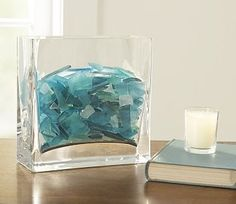 Sea glass in a vase. with a white candle. Simple pretty decor for bathroom! I think I'd put the white candle in a round vase filled with seaglass