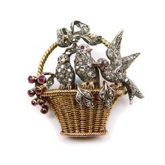 Antique diamond and gem set basket and bird brooch, c.1900, the woven gold tapering basket with ropetwist handle, three rose diamond set birds perched upon the rim, ruby set eyes, a diamond ribbon-tied bow to the basket handle, and a cabochon ruby budding stem emerging to the lefthand side, mounted in silver and gold Length 3.2cm / 1in''