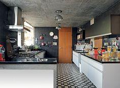 Nada comum em cozinhas, o espelho entre os armários reflete a luz que entra pelas grandes janelas – ideia da cenógrafa Claudia Terçarolli. As pastilhas de vidro pretas foram escolhidas pela facilidade de limpar (Foto: Marcelo Magnani/Casa e Jardim)
