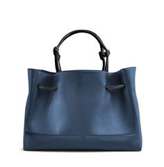 The Tote in Denim and Black from von Holzhausen made from natural grained soft Italian leather with painted edges. Shoulder straps elongate when worn for a comfortable fit. Features two open pockets on interior and removable signature wallet.