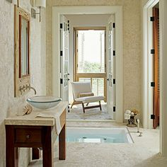 Asian Oasis                                         A sunken Japanese soaking tub looks supremely serene. Creamy stone on the floors and walls, and a simple wood vanity topped                                            with a glass-bowl sink contribute to the spa-like setting.