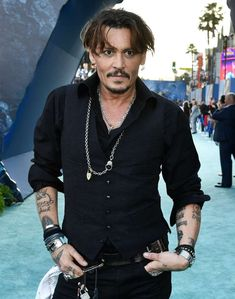 """Johnny Depp posing for a picture: Johnny Depp attends the premiere of """"Pirates of the Caribbean: Dead Men Tell No Tales"""" in Los Angeles on May 18, 2017."""
