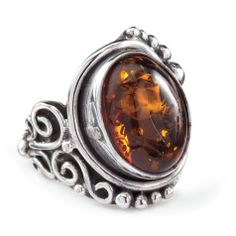 Amber Tiger Believed in the Far East to embody the souls of tigers, a substantial cabochon of genuine amber centers the intricate setting of this impressive, sterling silver ring. Handcrafted. Whole sizes 5-11. $69.95