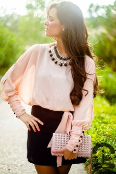 black pencil skirt with blush, cape sleeved blouse with a tie at the waist and a black and white pearl bib necklace