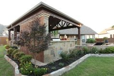 Patterned cedar edging add interest to this pavilion as does the stone half wall and textured concrete backing. By Outdoor Signature in Argyle, TX