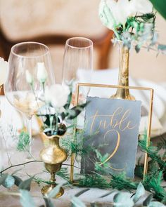 I love this frame for table numbers! The minimalistic gold edges tie in with the gold geometric details. Maybe the paper with the table number could be dark green with gold writing?
