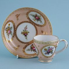 Late 18th century Chamberlain Worcester porcelain coffee cup & saucer, decorated with finely painted floral panels and gilding against a pale Salmon pink ground