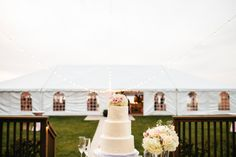 Beautiful blush and ivory cake at a tented wedding reception.
