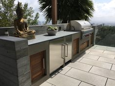Custom Design Studio Ma, Inc. outdoor concrete cooking space with built-in barbecue grill designed with wood cabinet doors and stainless steel refrigerator. Design also features concrete succulent planter and concrete paver patio. #patio #outdoorkitchen #outdoorcooking #outdoorcookingspace #outdoorliving #dreambackyard #outdoorkitchendesign #landscapearchitecture #landscapedesign #succulents #california #belair #californialiving #customkitchen #grill #barbecue #builtingrill #palmtrees…