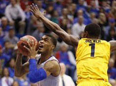 Kansas guard Frank Mason III (0) ducks under Kent State guard Kris Brewer (1) on his way to the bucket during the first half on Tuesday, Dec. 30, 2014 at Allen Fieldhouse. #KU