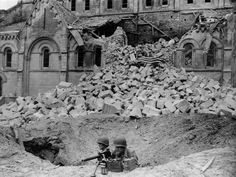 Covered with the American flag, the body of Maj. Thomas D. Howie, commander of the U.S. Army 3rd Battalion, 116 Infantry, rests amid the ruins of Saint Croix Church in Saint-Lô, France, while his men keep holding position behind their machine gun, July 19, 1944. (AP Photo/Harry Harris).