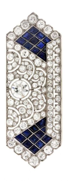 Mauboussin - An Art Deco platinum, old brilliant-cut diamond and buff-top sapphire brooch, French, circa 1926. With maker's mark and numbered. 5.5 x 2 cm.
