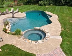 Beautiful pool with faux edge, sun shelf with umbrella, and raised stone coping spa with vanishing edge spillover | Yelp