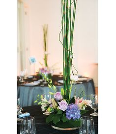 Flower arrangement uses horstails, purple hydrangeas, coolwater lavender roses, lilies, lavender dendrodium orchids & curly willows.
