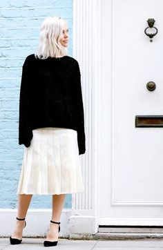 white pleated skirt and black sweater