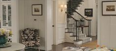 """The Change-Up movie house staircase """"It's not quite Colonial or Arts and Crafts but a pastiche of traditional elements. We noticed that a lot of houses in Atlanta had a similar style: dark floors, white cabinetry, iron railings, creamy walls, which we replicated with Benjamin Moore Linen White, and beautiful fabrics on windows and furniture."""""""
