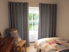 Lined Wave curtains in Swedish Stripe Seagrass.The Wave heading system gives a clean and stylish look with soft folds when drawn. The corded pole ensures the folds are evenly spaced across the window and the curtains fold back very neatly to the sides when open. This customer made a pieced cushion and bed throw in a selection of our fabrics to complement the room.
