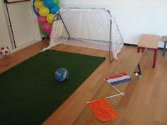 Poppen-/wisselhoek: voetbalveld met tribunebank en in kast oranje supporters kleding.