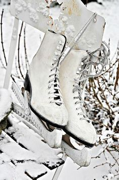 Antique Ice Skates on Weathered White Chair in the Snow