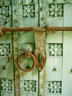 Ornately carved door with rusted knocker and lock
