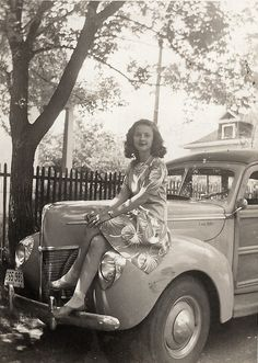 U.S. A young lady sitting on a car in Shrewsbury, Missouri, c.1945.