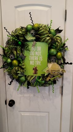 "This is a fun Star Wars Yoda deco mesh Lime green and black wreath. Complete with plush character Yoda and his famous quote ""Do or Do not there is no try"" sign in middle of the wreath. It's filled with fun green and black ornaments, fun ribbon and Curly Q's. Visit our Facebook page  Facebook.com/craftycrandallcreations"