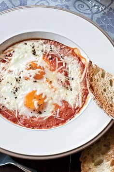 This baked egg recipe incorporates tons of summer flavors in the rich roasted tomato sauce to create the ultimate summer brunch recipe. Bake your eggs within a fresh tomato sauce, add oregano, garlic cloves, and top with parmesan cheese for a creamy and cheesy breakfast recipe. Once it's cooked, dip your toast into the runny yolks and the tomato sauce, and enjoy.#tomatorecipes #brunchrecipes #breakfastrecipes #eggrecipes #bakedeggs #tomatosauce #summerrecipes #summberbrunch Roasted Tomato Sauce, Tomato Sauce Recipe, Roasted Tomatoes, Egg Recipes, Brunch Recipes, Summer Recipes, Breakfast Recipes, Baked Eggs, Parmesan