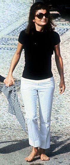 the timelessness of Jackie O...great look, as always.   On vacation, casual, but impeccably dressed.  White slacks and a black  T-shirt.  Add sandals and her trademark large sunglasses and you're ready to go.