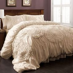 """Ruched comforter set in ivory with handmade floral embellishments.  Product: Queen: 1 Comforter and 2 standard shamsKing: 1 Comforter and 2 king shamsConstruction Material: 100% PolyesterColor: IvoryFeatures:  Handmade floral detailsRuched design Dimensions: Standard Sham: 20"""" x 26"""" Queen Comforter: 96"""" x 92"""" King Sham: 20"""" x 36""""  King Comforter: 110"""" x 96""""   Note: Shams do not include insertsCleaning and Care: Dry clean"""