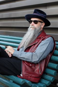 <3 You may be cool, but you'll never be Long silver beard, shade wearing, cigar-smoking man wearing a blue felt fedora and sleeveless leather jacket sitting on a blue bench cool.   . #PittiUomo87 Sir. @krammerandstoudt on #PHOTO by male® Jan. '15