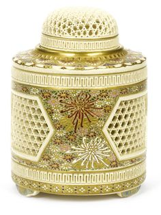 A Satsuma koro (incense burner) and cover By Kinzan, mid 19th century Painted in enamels and gilt, the cylindrical body supported on three short feet and pierced with three honeycomb-patterned hexagonal cartouches, separated by kiku-heads on a dense floral ground, the domed cover similarly reticulated, signed Satsuma Kinzan; with wood storage box.