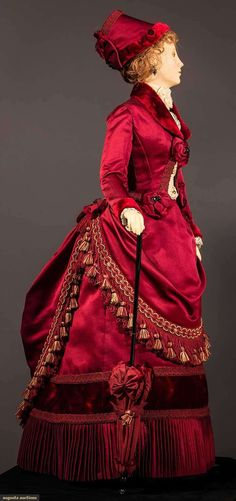 """29"""" figure, period accurate 1885 visiting dress created & hand sewn by fashion designer John Burbidge: deep red silk satin & velvet bustle skirt & jacket, lace blouse, fringed & tasseled over skirt, includes matching parasol & hat, shoes, undergarments, all excellent. This is one of 75 """"ladies"""" each costumed in a 1860 through 1914 unique ensemble, as seen in the book """"Les Petites Dames de Mode"""" & numerous museum presentations throughout the U.S."""