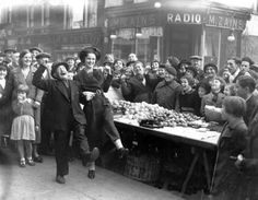 taken in Lambeth Walk in the 1938, entitled 'A Crowd Looks on as Miss Dipper Does the Lambeth Walk with Billy Pease the Peanut and Toffee King'