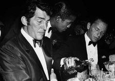 Dean Martin making sure Sammy Davis Jr. is filling Frank Sinatra's glass ALL the way up.