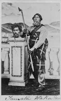 Portrait of Tamata Waka posed with axe-headed spear next to a superimposed bloody head on a pedestal. Photographer unknown.