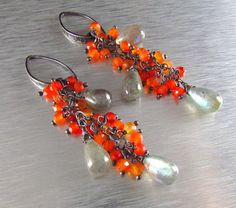 Faceted carnelian rondelles in various shades of orange, dangle amongst smooth labradorite drops. The labradorite has flashes of aqua blue and green. Each gemstone is wrapped with an oxidized sterling silver head pin, then attached to sterling chain. The earrings are finished off using textured sterling crescent shaped ear wires. The earrings measure 2 3/4 or 7cm. in length.