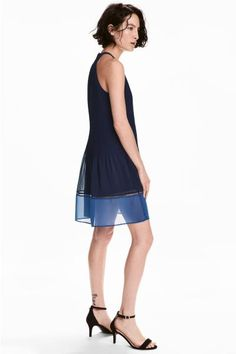 Sleeveless, pleated dress in an airy weave in a narrow cut at the top with an opening with a button at the back of the neck. Inset hemstitch embroidery and